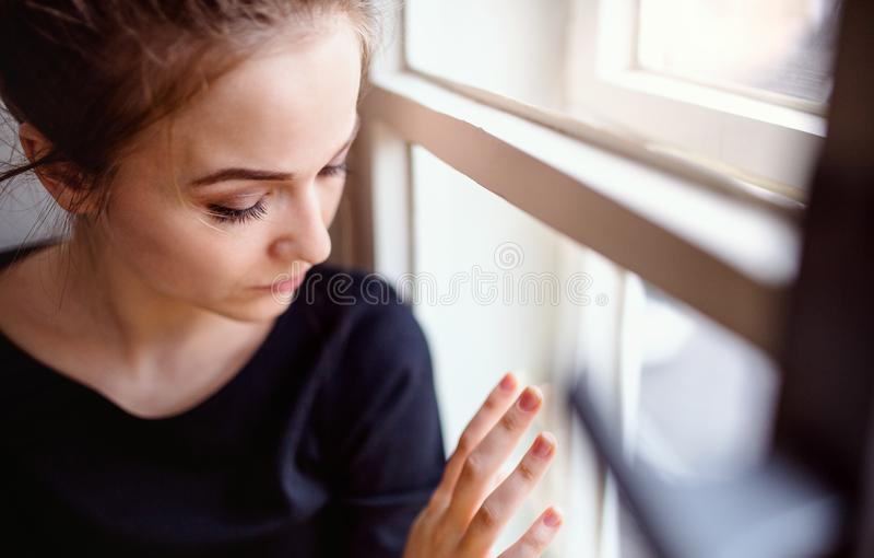 Eine Nahaufnahme der jungen traurigen Studentin, die auf Fensterbrett sitzt stockfotos