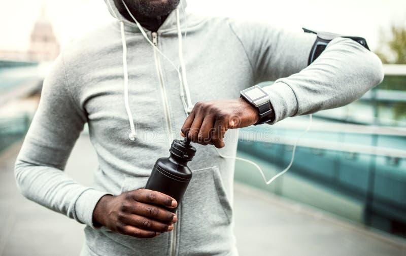 Eine Nahaufnahme des jungen sportlichen Läufers des schwarzen Mannes mit Wasserflasche in einer Stadt lizenzfreies stockbild