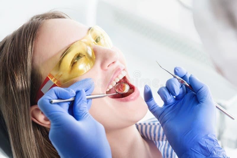 Eine Nahaufnahme des Mädchens wird von einem Zahnarzt mit offenem Mund und einer Serviette und geschlossenen Augen untersucht Zah lizenzfreies stockbild
