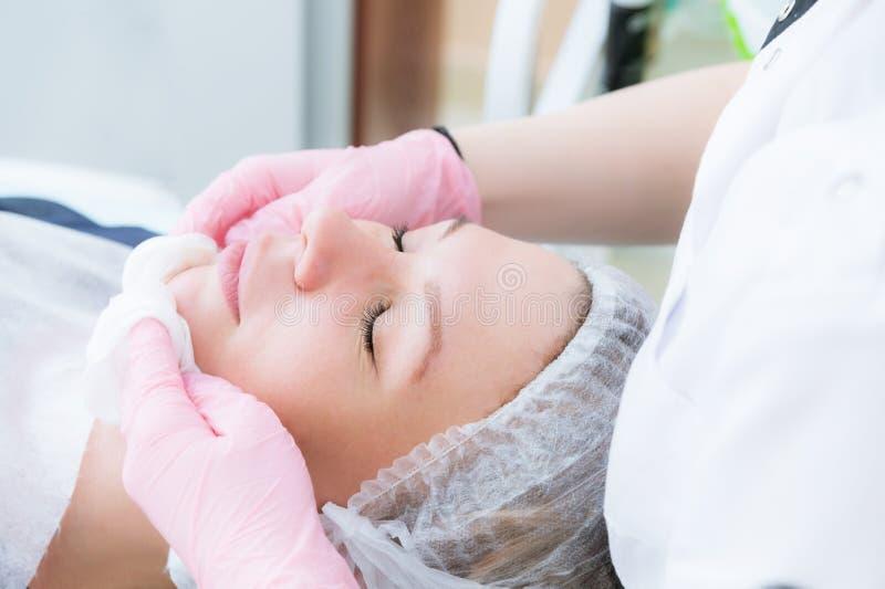 Eine Nahaufnahme des Reinigungsverfahrens im Büro von Cosmetology Die Hände des Cosmetologist in den rosa Handschuhen sind stockfotografie