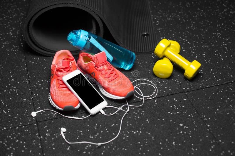 Eine Nahaufnahme des Turnhallenzubehörs für Sporttraining Stumm-Glocken, Flasche und Sportschuhe mit einem intelligenten Telefon  lizenzfreie stockfotos