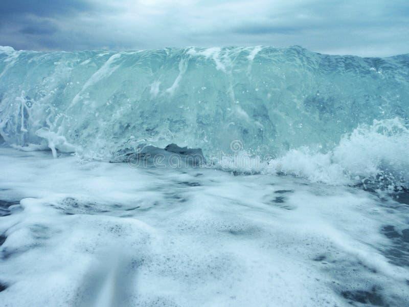 Eine Nahaufnahme einer schäumenden Welle, die auf dem Ufer bricht lizenzfreie stockfotografie