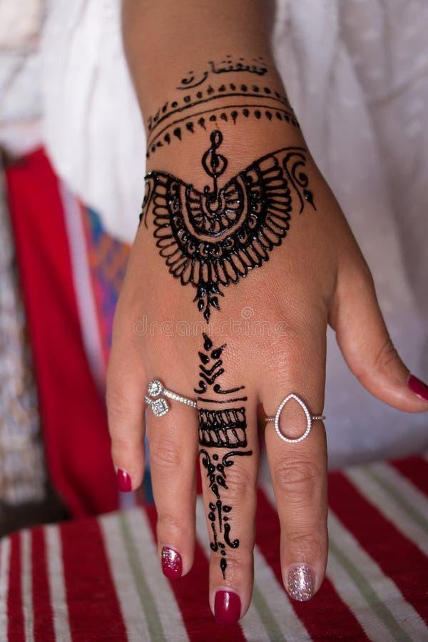 Eine Nahaufnahmehennastrauchtätowierung auf einer Frauenhand Mehndi ist eine Form der Körperkunst lizenzfreie stockfotos