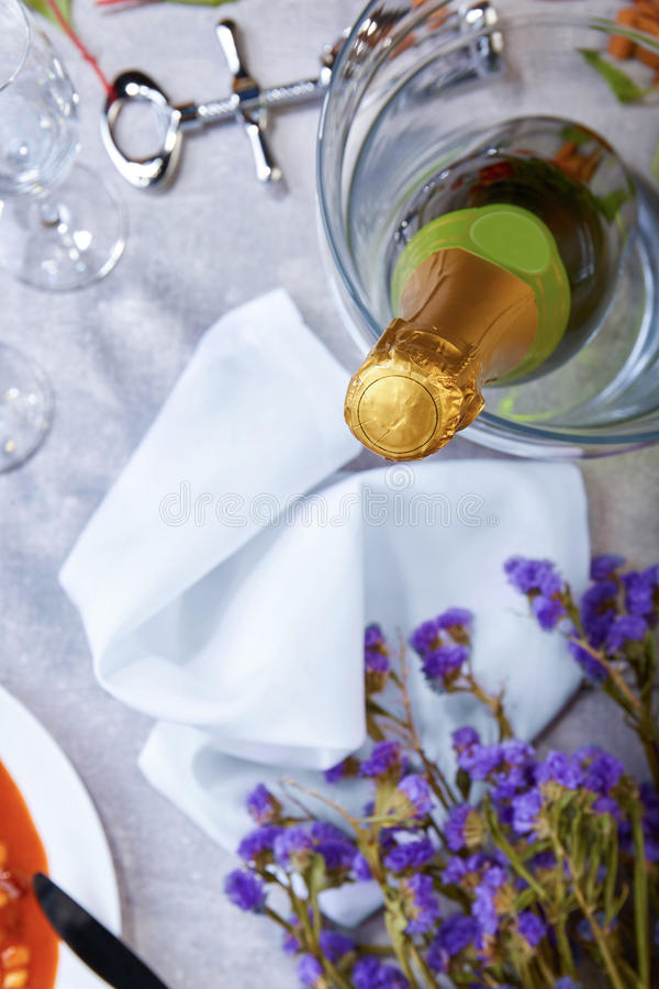 Eine nahe Flasche Champagner, schneeweiße Serviette, kleine purpurrote Blumen, Korkenzieher auf einem unscharfen Hintergrund lizenzfreie stockfotos