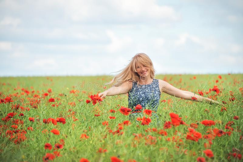 Eine natürliche Frau mit dem blonden Haar wirbelt auf einem Gebiet mit schönen roten Mohnblumen stockfotos