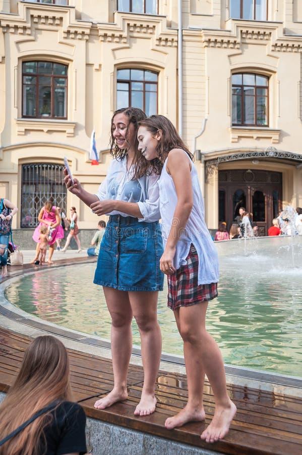 Eine nationale mexikanische Feier des Tages der Toten Zwei Mädchen durch getränkt im Brunnennehmen selfie lizenzfreie stockbilder