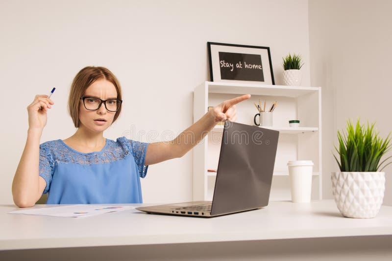 Eine nervöse junge Geschäftsfrau, die in weißen Büroraum zeigt stockfoto