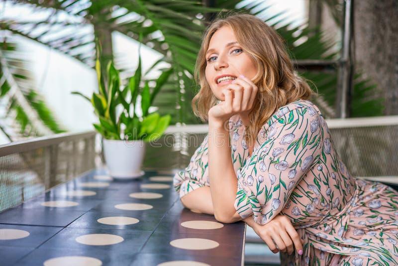 Eine nette Frau, die an einem Tisch in einem Café und in einem Lächeln sitzt stockbild