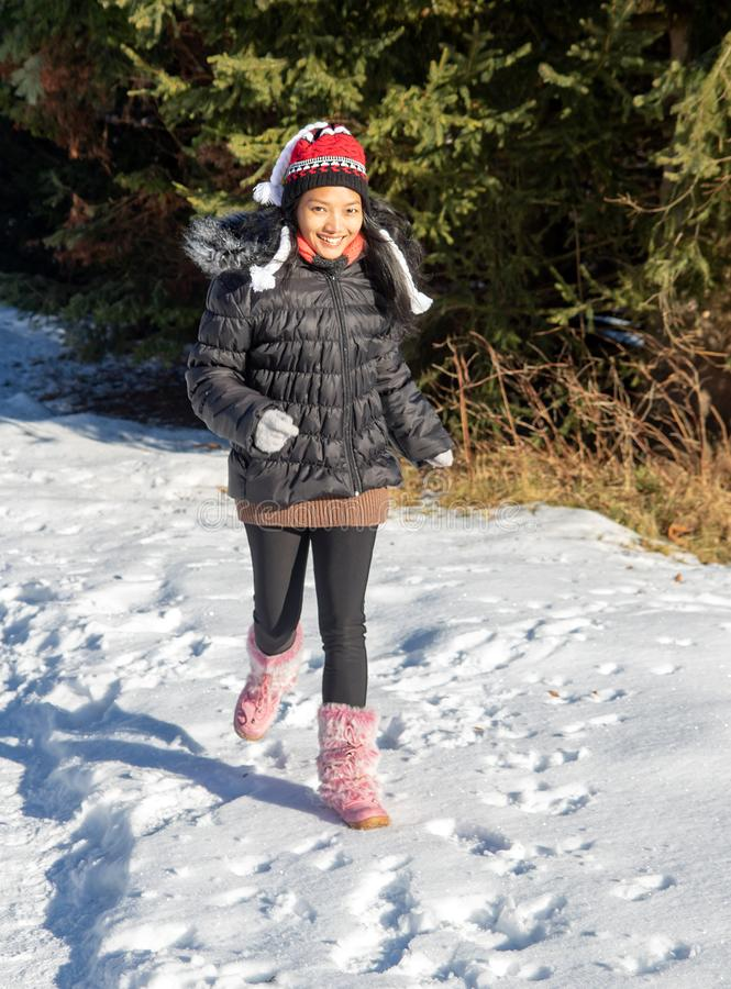 Eine nette Frau, die in eine schneebedeckte Natur läuft stockfotos