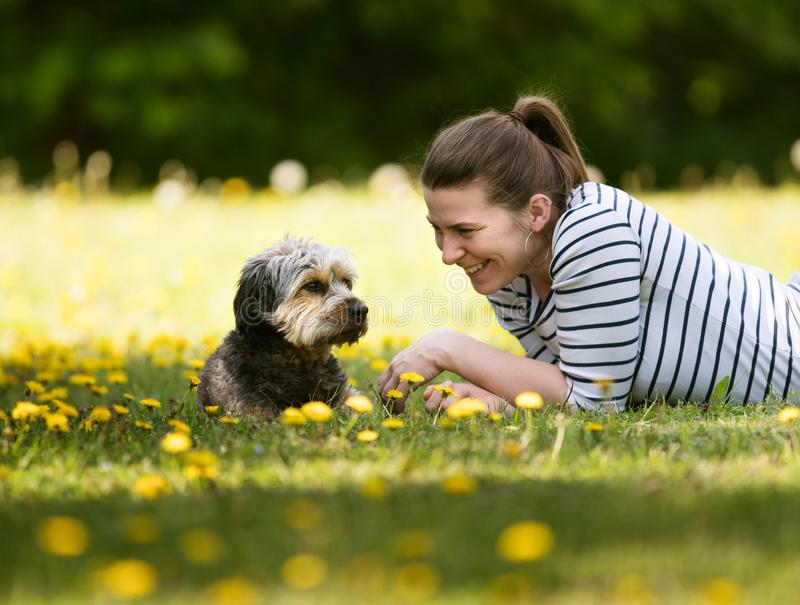 Eine nette, junge Frau, die auf dem Gras mit ihrem Haustier liegt stockfotos