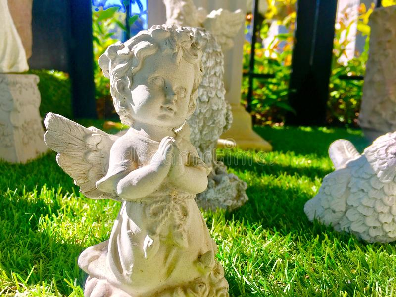 Eine nette kleine Engelsstatue auf dem Gras mit Sonnenlicht lizenzfreies stockfoto