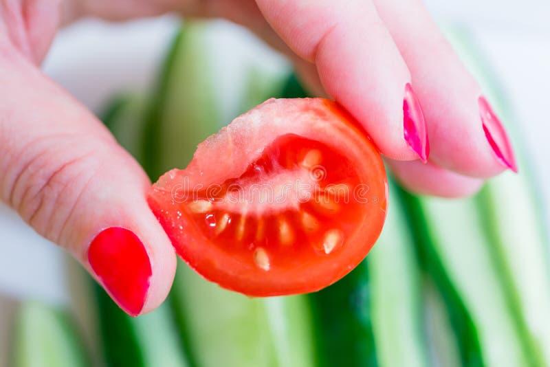 Eine neue Scheibe einer Tomate in einer Frau ` s Hand mit roten Nägeln auf dem Hintergrund eines Gurkensalats Nahrung der gesunde lizenzfreies stockfoto