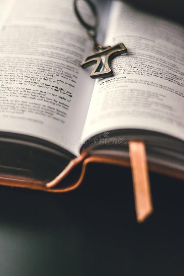 Eine offene Bibel wird auf eine schwarze Oberflächentabelle gesetzt stockbild