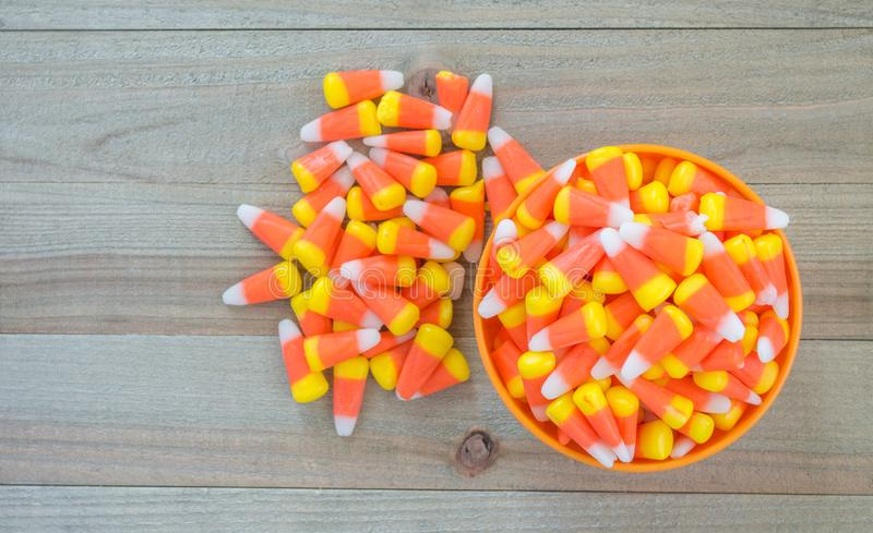 Eine orange Schüssel, die mit Süßigkeitsmais auf einem hölzernen Hintergrund überläuft lizenzfreie stockfotos