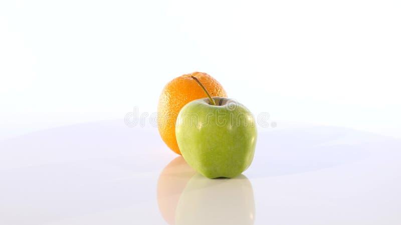 Eine Orange und ein grüner Apfel Die Frucht dreht sich langsam auf einen weißen Hintergrund lizenzfreie stockfotografie