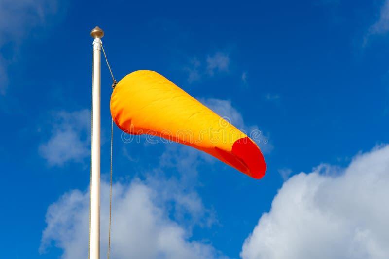 Eine orangefarbene Windsocke, die in der Brise auf einem Fahne mit blauem Himmel dahinter fliegt lizenzfreies stockfoto