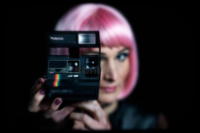 Eine originelle Polaroid-Kamera in der Hand eines alten Mädchens lizenzfreies stockbild
