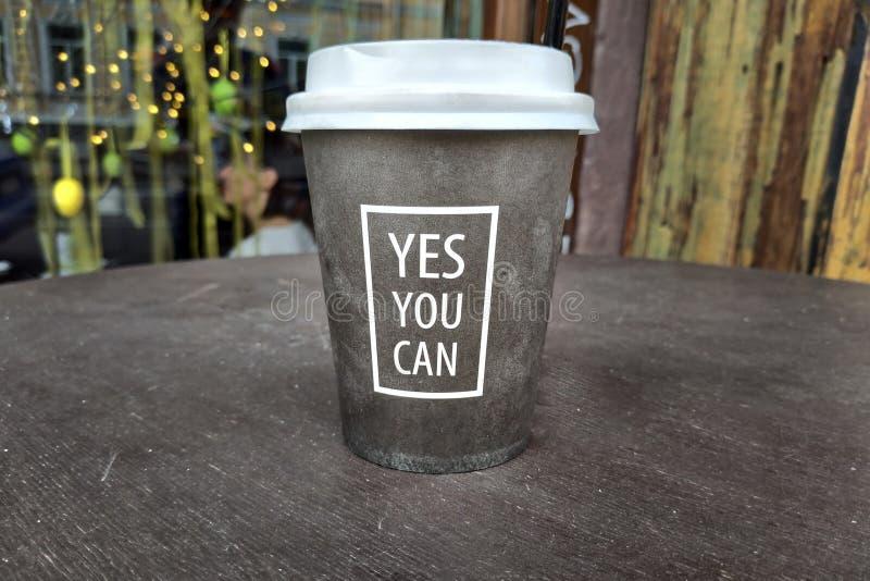 Eine Papierschale für Kaffee mit einem weißen Deckel ist auf dem Tisch stockfotos