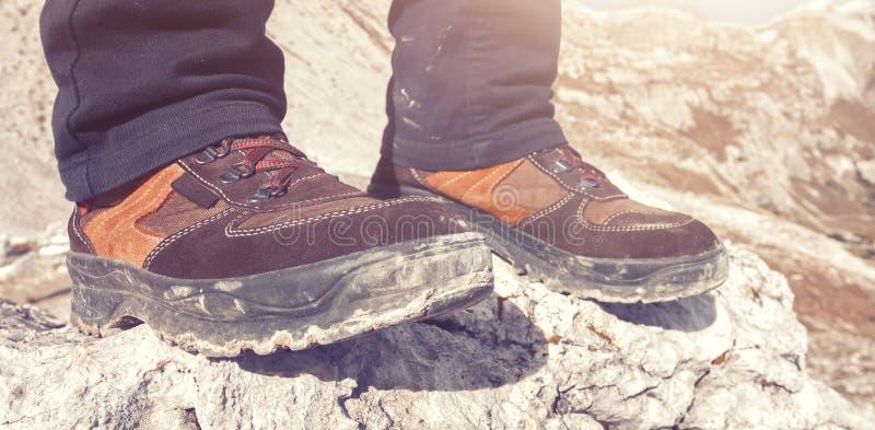 Eine Person, die auf die Oberseite einer Gebirgsfelsennahaufnahme wandert Schuhe steht lizenzfreie stockfotografie