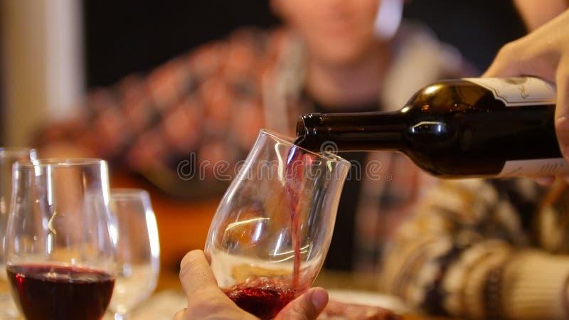 Eine Person, die den Wein im Glas gießt lizenzfreie stockbilder