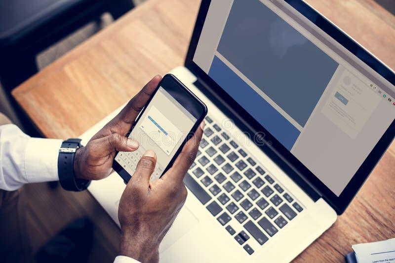 Eine Person, die einen Handy und einen Laptop verwendet stockbild