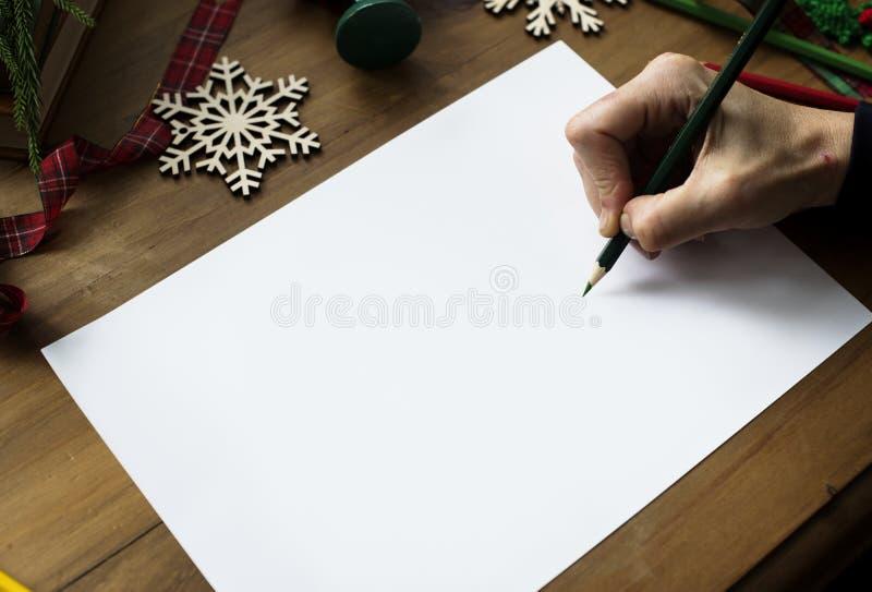 Eine Person, die sich vorbereitet, eine Weihnachtswunschliste zu schreiben stockbilder