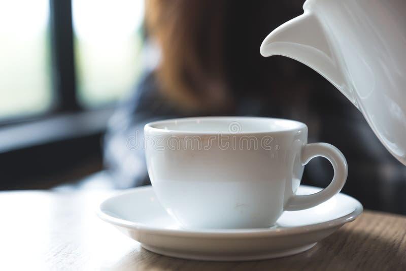 Eine Person, die Teekanne hält und Tee in eine weiße Schale auf Holztisch gießt lizenzfreies stockbild