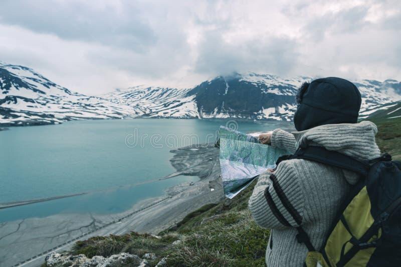 Eine Person, die Trekkingskarte, drastischen Himmel auf Dämmerung, See und schneebedeckte Berge, nordisches kaltes Gefühl betrach stockfotos