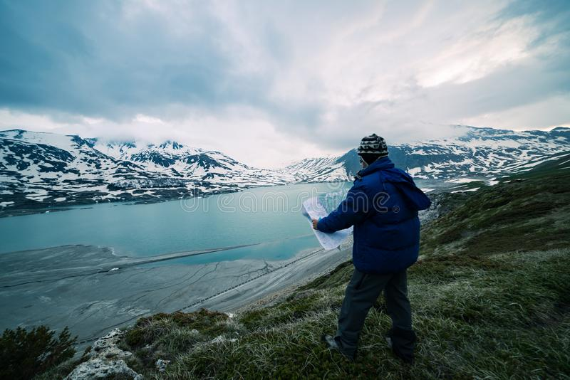 Eine Person, die Trekkingskarte, drastischen Himmel auf Dämmerung, See und schneebedeckte Berge, nordisches kaltes Gefühl betrach lizenzfreies stockfoto