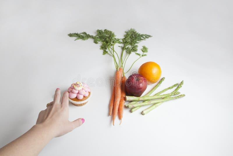 Eine Person ` s Hand, die für einen kleinen Kuchen anstelle der Früchte und Veg erreicht lizenzfreies stockfoto