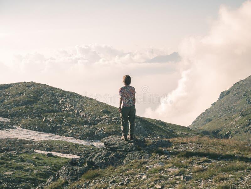 Eine Person, welche die Ansicht hoch oben auf den Alpen betrachtet Expasive-Landschaft, idyllische Ansicht bei Sonnenuntergang Hi lizenzfreies stockfoto