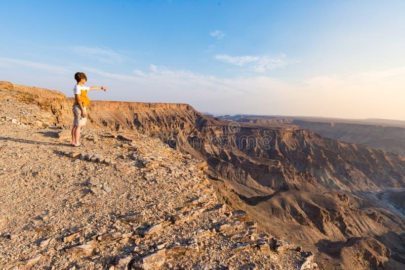 Eine Person, welche die Fisch-Fluss-Schlucht, szenisches Reiseziel in Süd-Namibia betrachtet Ausdehnende Ansicht bei Sonnenunterg lizenzfreies stockbild