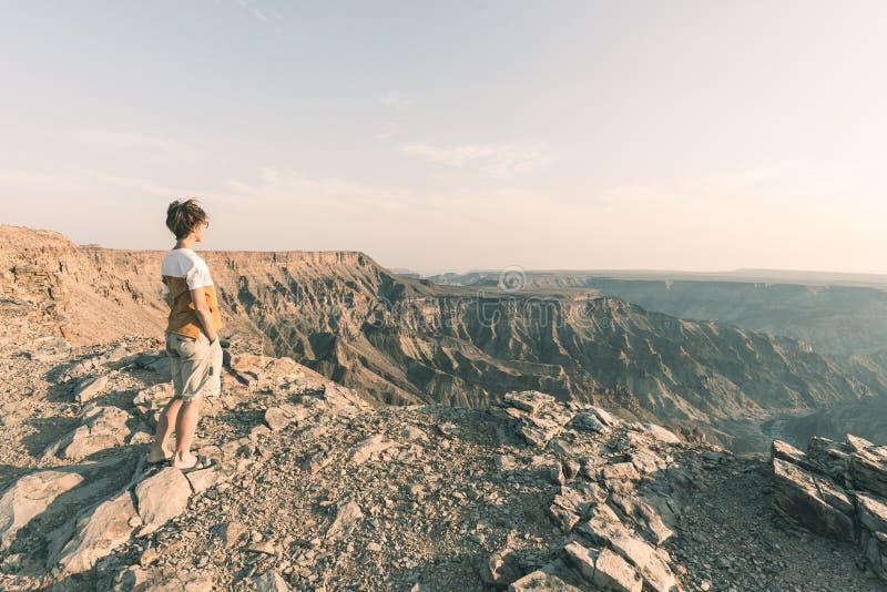 Eine Person, welche die Fisch-Fluss-Schlucht, szenisches Reiseziel in Süd-Namibia betrachtet Ausdehnende Ansicht bei Sonnenunterg stockfotografie