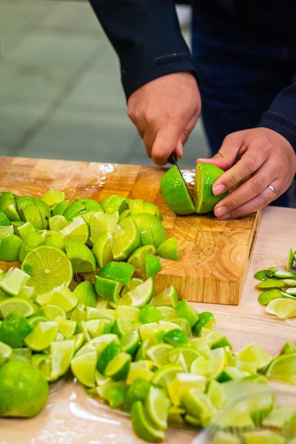 Eine Person, welche die Zitrone mit scharfem Messer für ein Gruppenparteiereignis schneidet lizenzfreies stockfoto