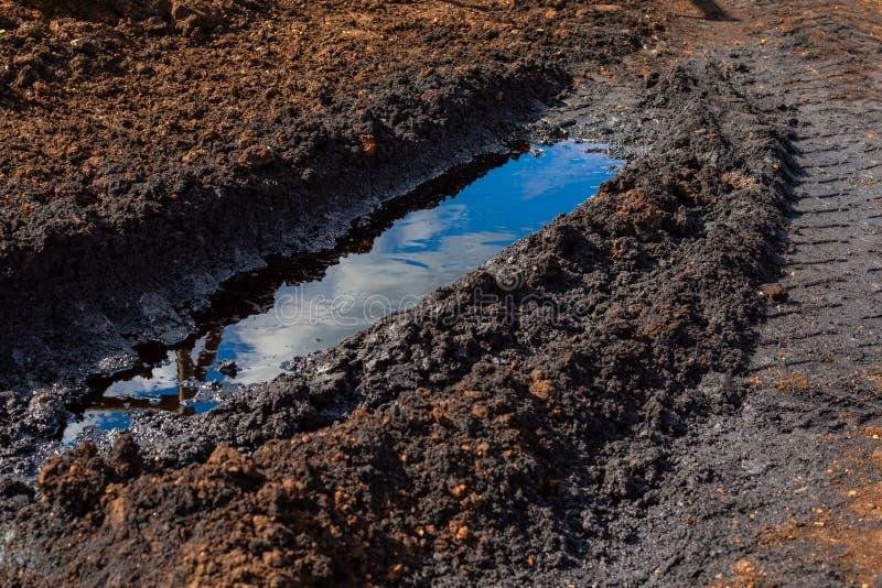 Eine Pfütze des verschütteten Rohöls in der Furche vom LKW Klimaunfall, Verschmutzung, Schaden der Umwelt stockbild