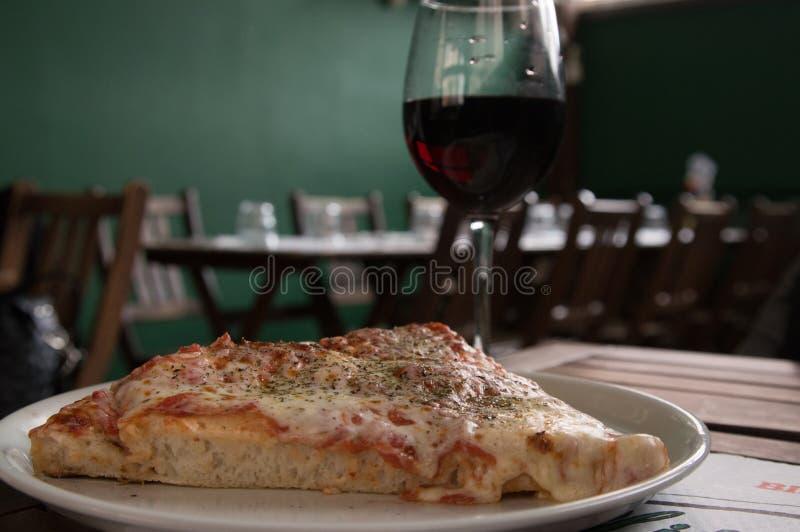 Eine Pizzascheibe auf einer Platte lizenzfreies stockbild