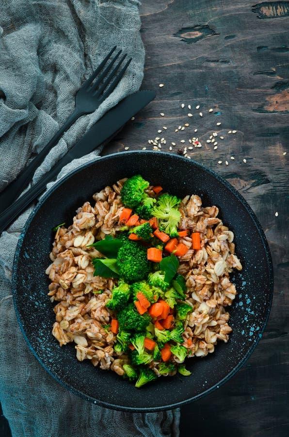 Eine Platte des gesunden Lebensmittels Hafermehl mit Brokkoli, Karotten und Petersilie lizenzfreie stockfotos