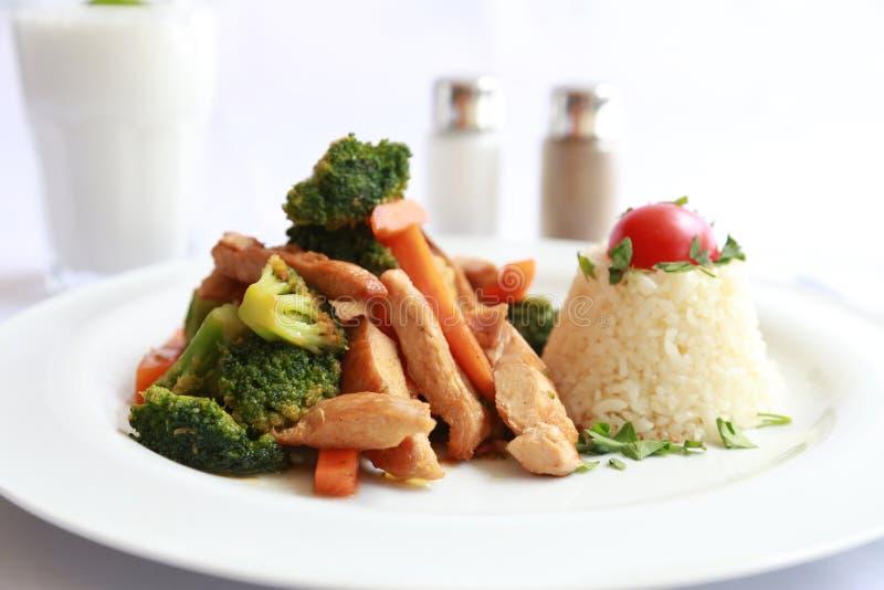 Eine Platte mit gegrilltem Huhn und Gemüse und Reis stockbilder