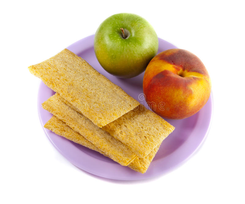 Eine Platte mit grünem Apfel, Pfirsich und drei Chipsletten stockfotografie