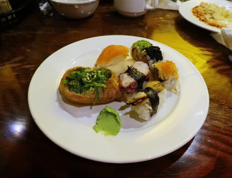 Eine Platte voll von Sushi mit einem Klecks von Wasabi stockfotos
