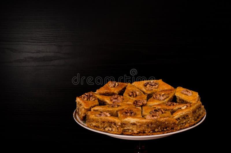 Eine Platte von Baklava mit Honig auf einem schwarzen Hintergrund, traditionelle türkische Bonbons Rombus lizenzfreies stockbild
