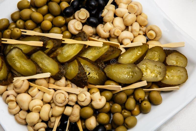 Eine Platte von Essiggurken auf einem Buffettisch Auswahl von marinierten Pilzen, gesalzene Gurken, Oliven, Senf in den Bohnen stockfotos