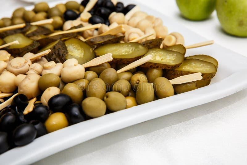Eine Platte von Essiggurken auf einem Buffettisch Auswahl von marinierten Pilzen, gesalzene Gurken, Oliven, Senf in den Bohnen lizenzfreie stockbilder