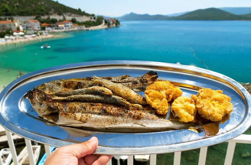 Eine Platte von gegrillten Fischen und eine schöne Ansicht des blauen Meeres stockbild