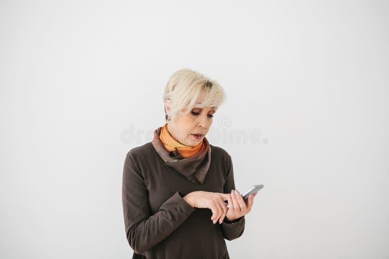 Eine positive moderne ältere Frau hält einen Handy und benutzt ihn Die ältere Generation und die moderne Technologie stockfotos