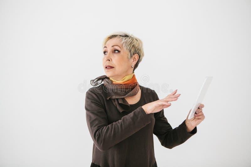 Eine positive moderne ältere Frau hält eine Tablette in ihren Händen und benutzt sie Die ältere Generation und die moderne Techno stockbild