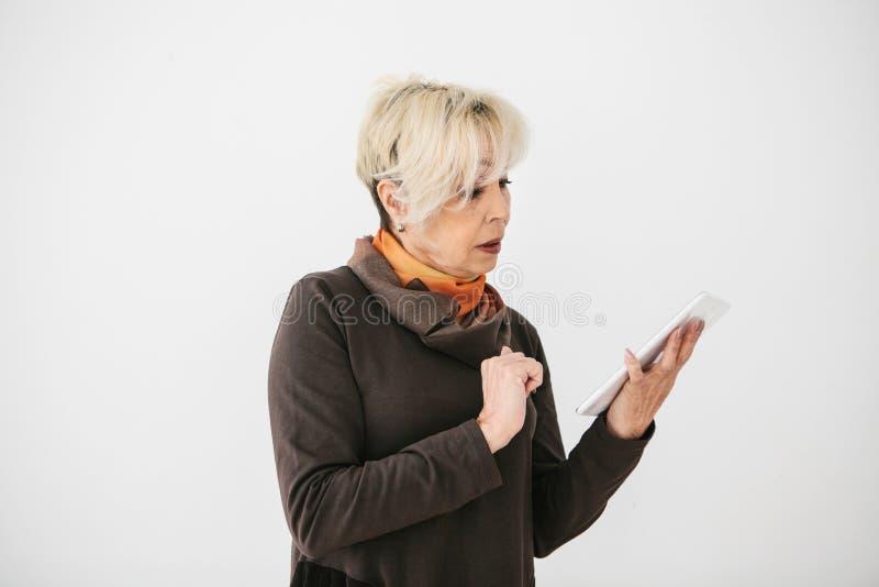 Eine positive moderne ältere Frau hält eine Tablette in ihren Händen und benutzt sie Die ältere Generation und die moderne Techno stockfoto