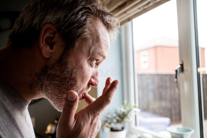 Eine Profilansicht eines Mannes, der seine Finger nachdem dem Essen in leckt stockfoto