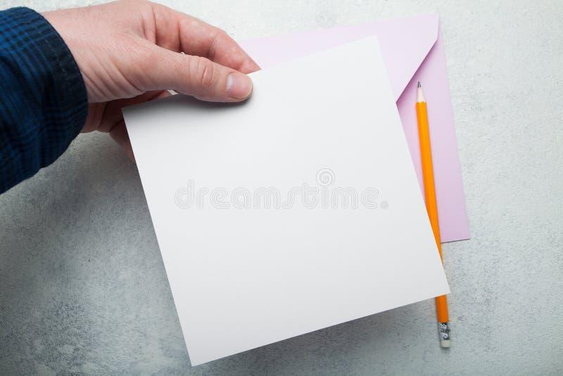 Eine quadratische Einladung für einen Feiertag in der Hand auf einem weißen Hintergrund lizenzfreie abbildung