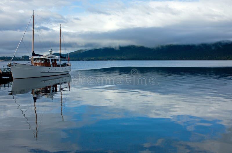 Eine Reflexion eines Bootes und des Himmels auf dem See Te Anau in Fiordland in der Südinsel in Neuseeland stockbild